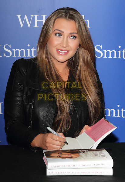 Lauren Goodger.(TOWIE & Dancing on Ice Star) signs 'Secrets Of An Essex Girl', her new book,  WH Smith, The Liberty Shopping Centre, Romford, Essex, England..16th February 2013.half length signing autographs black leather jacket table .CAP/JIL.©Jill Mayhew/Capital Pictures