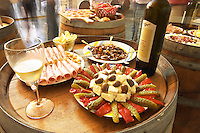 Bottles of wine and Albanian appetizers: cheese olives sausage, min-pizzas, chips, crisps, nuts, sheep cheese, cornichons, bell pepper, and more. A glass of wine. Cobo winery, Poshnje, Berat. Albania, Balkan, Europe.