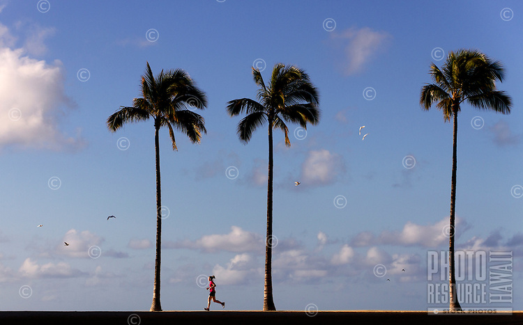 A woman enjoys a run on a beautiful, pristine morning on O'ahu.