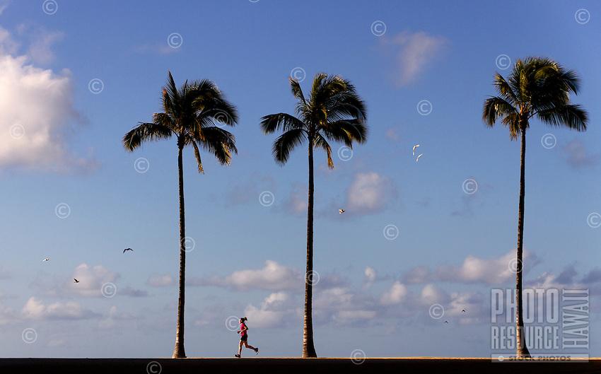 A woman enjoys a run on a beautiful, pristine morning on O'ahu.