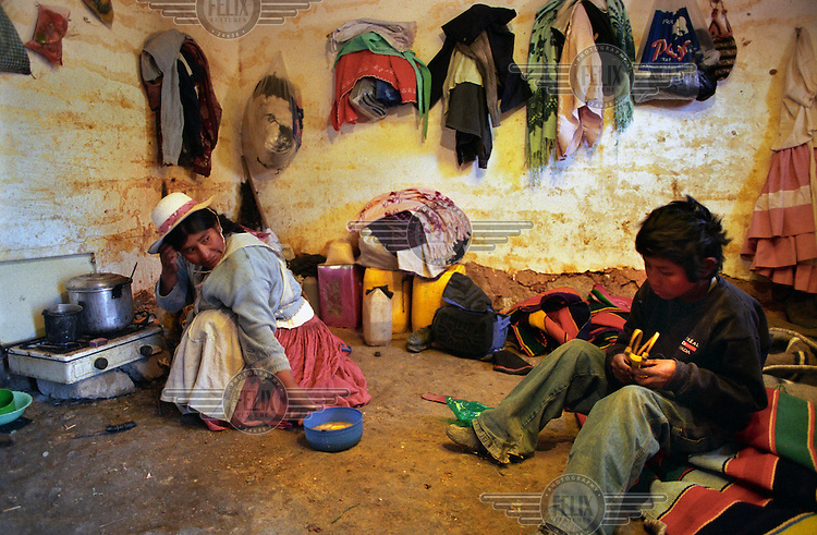 37 year old Angelica Solice serves her 11 year old son, Santiago soup for breakfast. They live on Cerro Rico (rich mountain), scouring for the remains of silver in the discarded rocks from the mine...