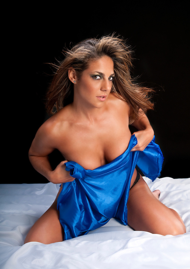 Hispanic Woman in Silk sheet naked in the bed with very sensual pose.