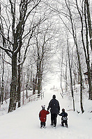 A parent and two children walk in the snow-covered woods.