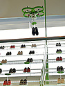 """March 7, 2015, Tokyo, Japan - A drone flies to the shelves and fetches a pair of tennis shoes to an awaiting customer at the """"flying shoe shop"""" in Tokyo on Saturday, March 7, 2015. As a customer uses an iPad to place an order, the drone takes off and delivers the requested pair from as many as 80 shoes displayed on a special stand, about 5 meters high and 10 meters wide.(Photo by Natsuki Sakai/AFLO) AYF -mis-"""