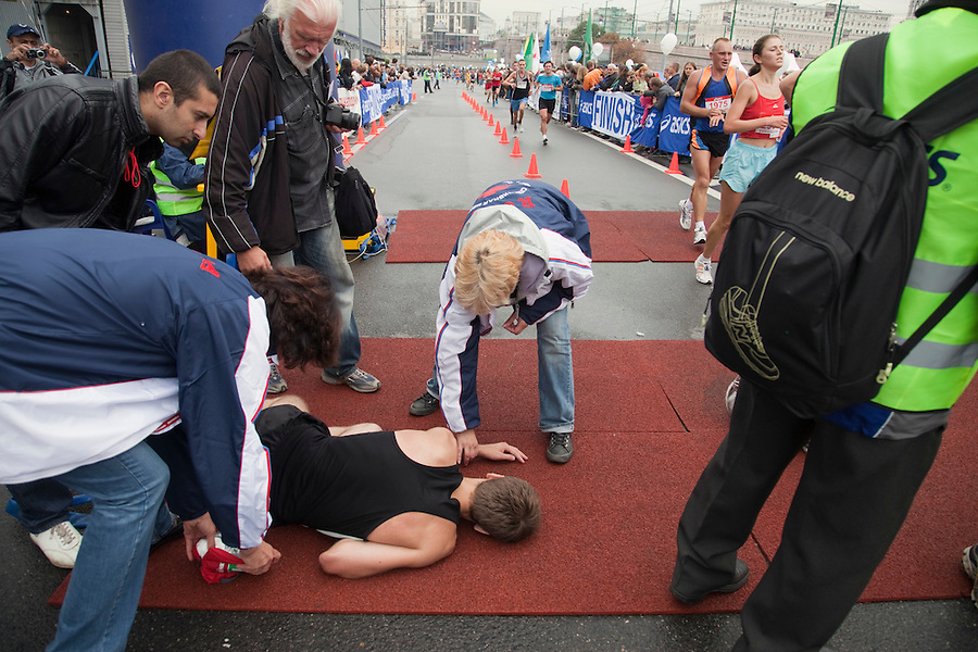 Moscow, Russia, 12/09/2010..A first aid worker takes the pulse of a runner who collapsed after crossing the finish line at the 30th annual Moscow International Marathon.