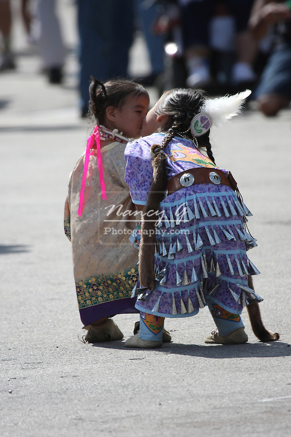 Two Native American children, sisters, kissing at a Pow Wow at the Milwaukee Lakefront Indian Summer Festival, Wisconsin
