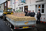 © Joel Goodman - 07973 332324 . 6 December 2013 . Marple , UK . The coffin arrives at The Royal Oak pub in Mellor .The funeral of farmer Bob Watson . His son David Watson drives his father's coffin on a trailer hooked to the back of Bob's favourite tractor through Marple via Bob's local pub before taking it on to the church . Photo credit : Joel Goodman