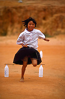 Girl running and jumping, northern Thailand