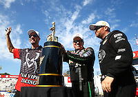 Nov 10, 2013; Pomona, CA, USA; NHRA funny car driver John Force (center), top fuel dragster driver Shawn Langdon (right) and pro stock motorcycle rider Matt Smith celebrate with the championship trophy during the Auto Club Finals at Auto Club Raceway at Pomona. Mandatory Credit: Mark J. Rebilas-