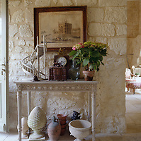 A cluttered hall table stands against  a rough-hewn stone wall