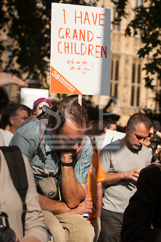 A demonstrator sits dejectedly under a placard which says 'I Have Grandchildren and so do lots of you!!' in front of the Houses of Parliament during the Climate Change demonstration, London, 21st September 2014. © Sue Cunningham
