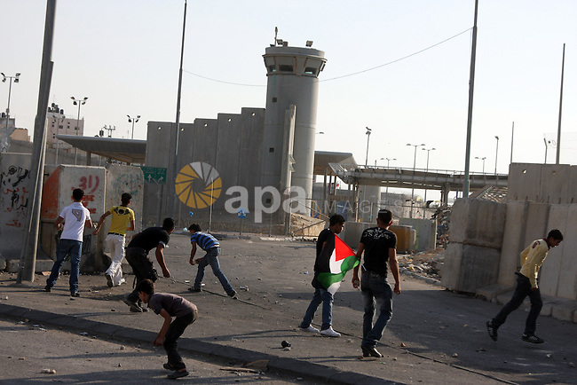 Palestinian youths throw stones at  Israeli border police during clashes at the Kalandia checkpoint near the West Bank city of Ramallah October 9, 2009. Palestinian leaders on Thursday called for a one-day general strike and warned of more street protests over Jerusalem, where clashes at the flashpoint al-Aqsa mosque two weeks ago cranked up tensions in the disputed city. Israel is playing down Palestinian warnings that its security tactics risk a new Palestinian uprising. Photo by Issam Rimawi