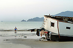 A foreign tourist swims in the sea next to a gutted boat on Patong beach the day after the tsunami hit the coast. On December 26, 2004, a major earthquake generated tsunamis that ravaged coastlines from Southeast Asia to Africa. Approximately 275,000 people were killed and tens of thousands were left homeless, making it one of the deadliest natural disasters in modern history.