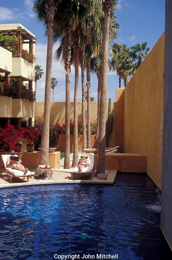 Tourists relaxing and reading books next to a hotel swimming pool in the town of San Jose del Cabo, Baja California Sur, Mexico