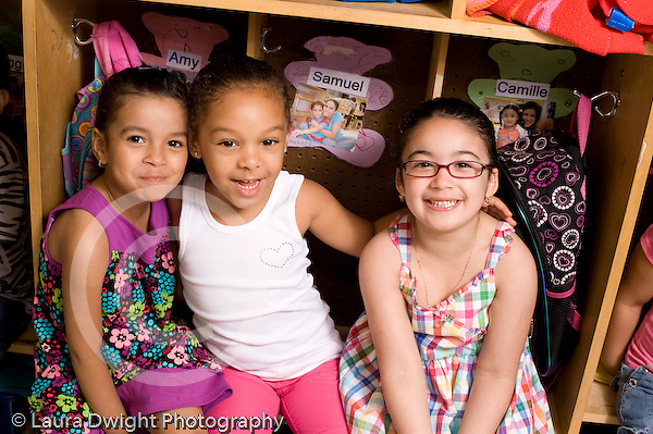 Preschool ages 3-5 portrait of three girls sitting in cubbies happy smiling horizontal
