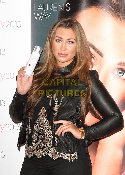 Lauren Goodger.appears at the Professional Beauty Show at Excel Centre, London, England..February 25th 2013.half length black leather jacket gold embroidered top hand on hip bottle.CAP/ROS.©Steve Ross/Capital Pictures.