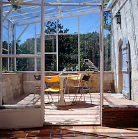 A lean-to glass-paned conservatory empty of plants is home instead to a small table and four coloured plastic chairs