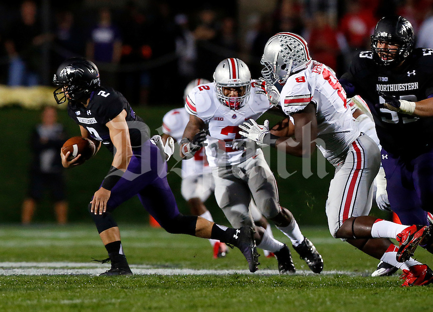 Northwestern Wildcats quarterback Kain Colter (2) carries the ball while almost tackled by Ohio State Buckeyes linebacker Ryan Shazier (2) in the first quarter of their game at Ryan Field in Evanston, IL on October 5, 2013. Columbus Dispatch photo by Brooke LaValley)