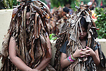 "A mother and daughter pray in front of the Catholic church during the annual Taong Putik, or ""mud people,"" festival in Bibiclat, on Luzon island, Philippines. The festival honors St. John the Baptist, and devotees cover their bodies with mud, banana leaves and vines to symbolize the animal skins the saint wore in the Bible. June 24, 2011."
