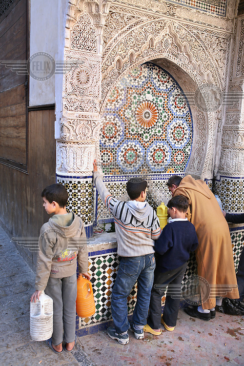 People collect drinking water at a fountain near the Najjarine Complex in the Fes medina. In Moroccan cities every neighbourhood used to have its own fountain but due to misuse and water waste many have closed.