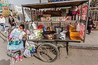 Jian bing street food vendor sleeping next to her food cart in Datong, China