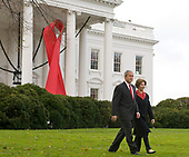 United States President George W. Bush and first lady Laura Bush, walk in front of a  large red ribbon to deliver remarks on World Aids Day on the North Lawn of the White House in Washington, D.C., Monday, December 1, 2008.<br /> Credit: Mannie Garcia / Pool via CNP