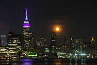 HOBOKEN, NJ - APRIL 11: The Empire State Building lit purple and gray in honor of the 100th anniversary of the New York state police while the moon rise over middle Manhattan as it is seen from shore on April 11, 2017 in Hoboken, New Jersey. Since April 11, 1917, the State Police have been committed to helping New Yorkers by providing them with friendly, professional service. Photo by VIEWpress/Eduardo MunozAlvarez