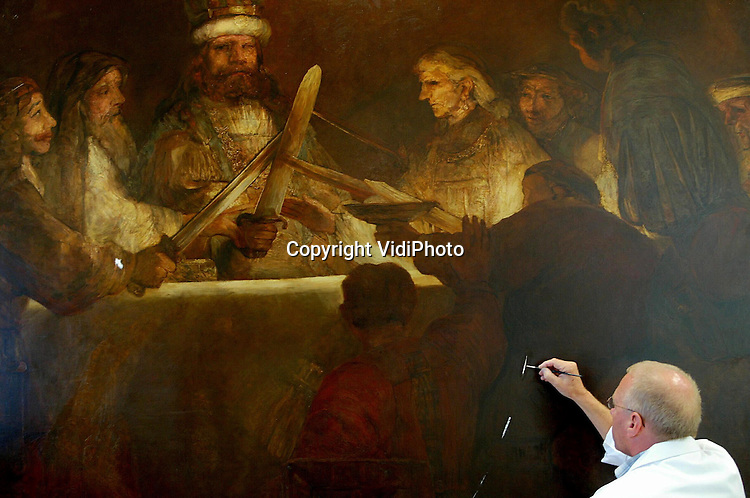 """Foto: VidiPhoto..NIJMEGEN - In het Valkhofmuseum in Nijmegen wordt op dit moment het imposante schilderij """"De samenzwering van de Batavieren"""" gestaureerd: een exacte kopie uit 1926 van een schilderij van Rembrandt dat in het Rijksmuseum in Stockholm hangt. Omdat het museum weigert dit megaschilderij uit te lenen, mag het Valkhof deze eveneens kostbare replica gebruiken. Het handelt over de opstand van de Bataaf Julius Civilis tegen de Romeinen. Over twee weken start in het Valkhofmuseum een voor Nederland unieke expositie over dit """"verdwenen volk"""". Foto: Restaurator Jan Broekhoff aan het werk."""