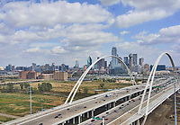 A Dallas skyline view of the city through the new Margaret McDermott bridge in downtown with nice puffy white clouds and blue sky. Dallas skyline stock photos.