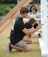 NWA Democrat-Gazette/ANDY SHUPE<br /> Connor Pocta, a freshman at the University of Arkansas from Huntington Beach, Calif., paints words Tuesday, Sept. 29, 2015, onto a block wall while participating in The Writing on the Wall Project sponsored by University Housing on the university campus in Fayetteville. Members of the campus community are encouraged to write hurtful words and names that they have experienced while on the university campus during this week. The wall will then be demolished using sledgehammers during a ceremony at 11 a.m. Friday.