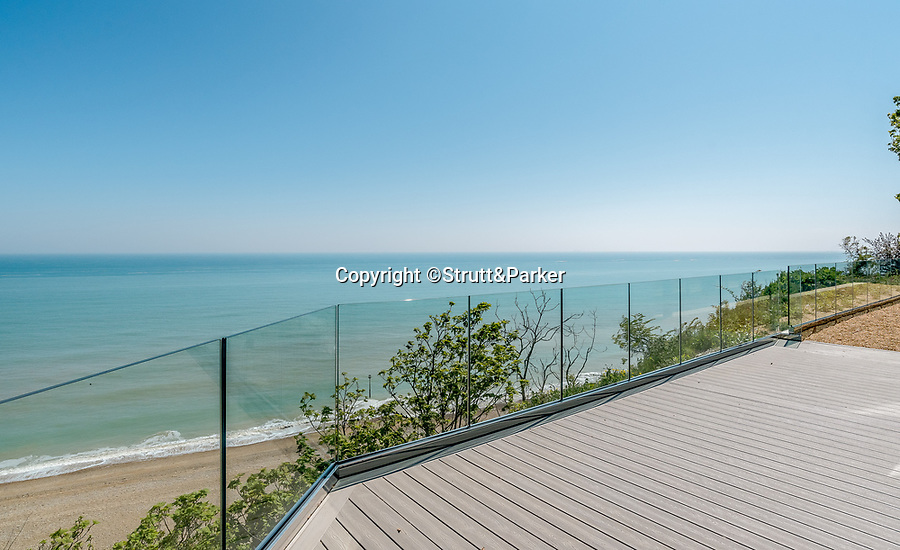 BNPS.co.uk (01202 558833)<br /> Pic: Strutt&Parker/BNPS<br /> <br /> Stunning rooftop terrace views...<br /> <br /> A former WW2 battery, with unrivalled views across the channel to France, has come on the market - but you'll need deep pockets to shell out on its stunning location.<br /> <br /> The cliff top gun emplacement was rapidly constructed in 1940, as Britsh troops were fleeing Dunkirk, and has now been transformed into a £6million 'James Bond style' property.<br /> <br /> The Gunnery, near Kingsdown in Kent offers 'incredible' views of the Channel, with the iconic White Cliffs of Dover visible to the west, and France to the south, while also coming with six acres of sandy beach.<br /> <br /> The unique 82ft long property is accessed by an underground tunnel that leads through the cliff to a glass lift which travels up to it. Another secret tunnel inside the four bedroom home, which is just a few feet from the cliff edge, provides passage to a home cinema.<br /> <br /> The 50ft long living room has floor to ceiling windows and the original gun loops can still be seen.