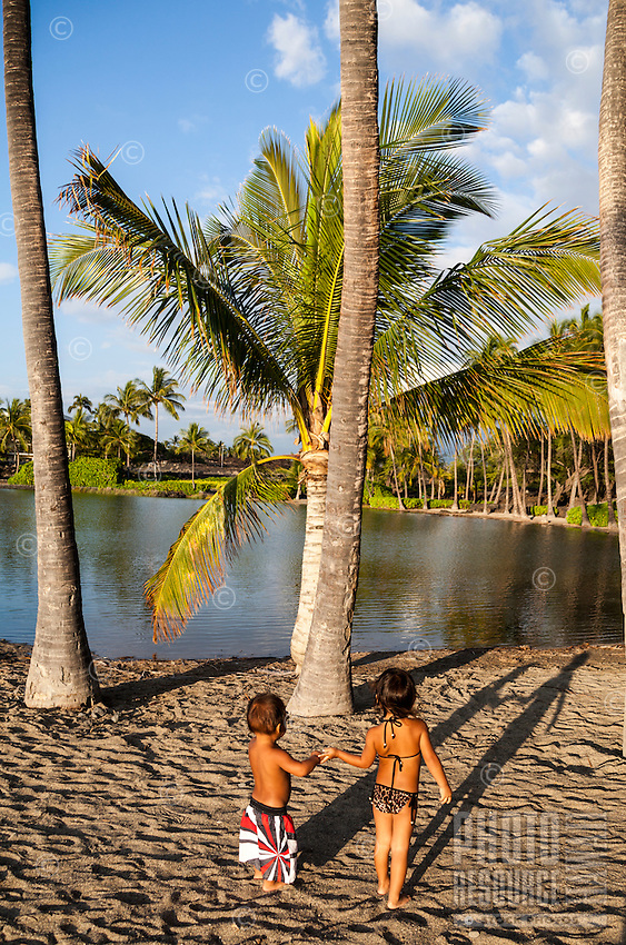 Children play by the historic fish pond at 'Anaeho'omalu Beach in Waikoloa, Big Island of Hawai'i