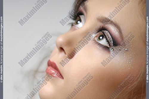 Stock photo of a Young woman beautiful face with artistic make-up decorated with strass stones Artistic close-up portrait