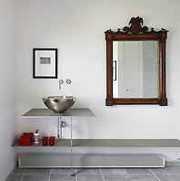 A large antique mirror on the bathroom wall contrasts with the otherwise minimal fittings of the steel and chrome basin and shelving unit