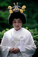 At a wedding in Tokyo, Japan, the bride wears a traditional white kimono, known as the shiromoku, but she has piled her hair up and decorated it with a small tiara and flowers instead of wearing the white hat which strict tradition would demand.