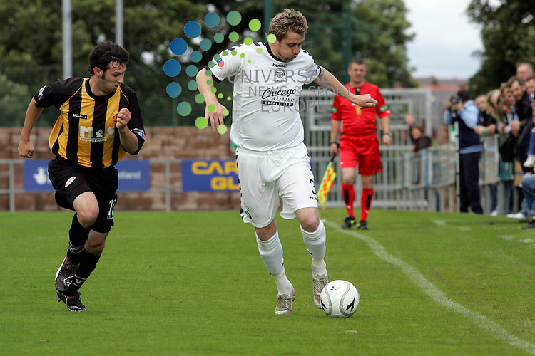Shires David Dunn getting the ball under control with Graeme Bell giving chase