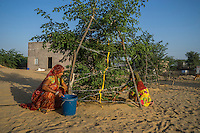 Manju Devi, 25, and her niece Anita Devi, 17, tend to a tree in her backyard plantation of forest trees behind her house in Rajera village, Bikaner, Rajasthan, India on October 23, 2016. Non-profit organisation Technoserve works with farmer's wives in Bikaner, providing technical support and training for backyard plantations that help these communities cope with the harsh climate of the Thar desert. The forest trees provide shade to the people and their cattle, reduces water loss and sand shifting, raises the value of their properties by improvement of the landscape and raises the pride of their families, ensuring better opportunities for their children. Photograph by Suzanne Lee for Technoserve