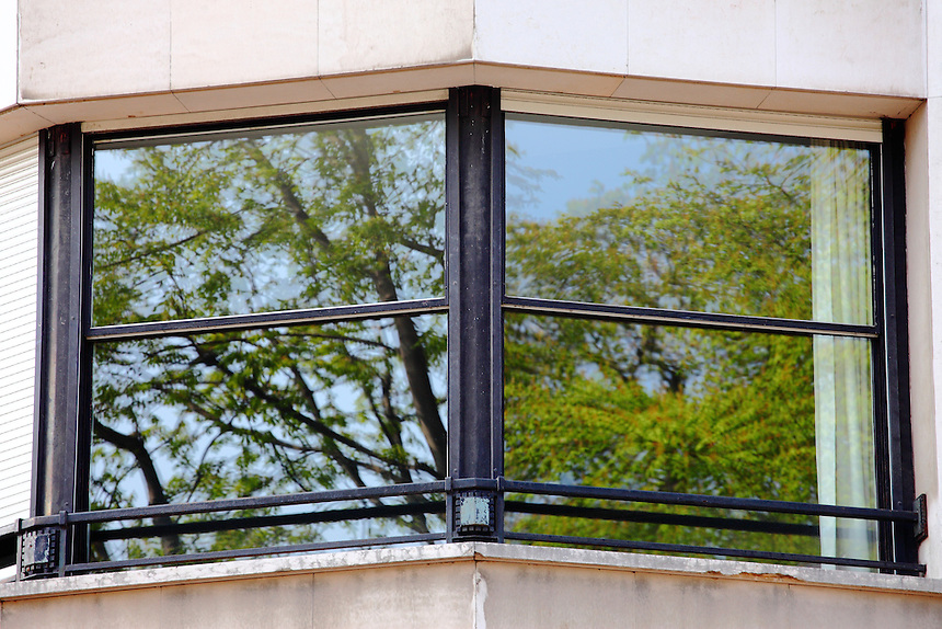 Paris Left Bank: A closed modern window with mirror glasses in front of the Luxembourg gardens, that reflects the green tree tops.<br />