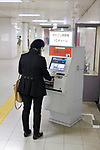 Woman using a fare adjustment machine at a subway station to pay the extra commute fare, Kyoto, Japan 2017