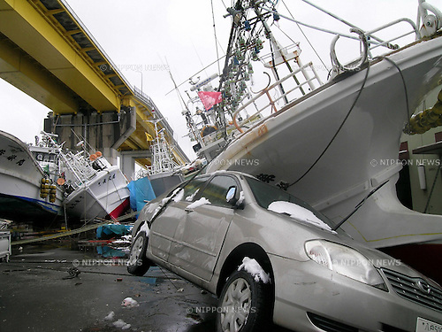 "March 16, 2011, Miyako, Iwate Prefecture, Japan - A passenger car is smashed beneath the ""Hokushi Maru, III"" a fishing boat in Hachinohe Port, Aomori Prefecture, Japan, after the Tohoku-Kanto Natural Disaster. (Photo by Mainichi Newspaper)"