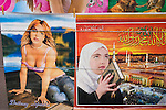A picture of Britney Spears hangs next to a poster of an Muslim women holding a Koran with a scene from Mecca behind her at a poster seller's stall in the Karikoo market in Dar Es Salaam, Tanzania.