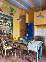 A vibrant yellow kitchen with blue painted beams. The room is furnished with a mix of vintage and salvaged pieces.
