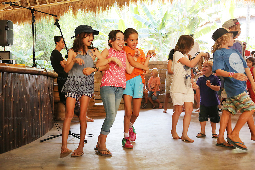Primary school students enjoying end of week song, dance, charade drama session<br /><br />The Green School (Bali) is one of a kind in Indonesia. It is a private, kindergarten to secondary International school located along the Ayung River near Ubud, Bali, Indonesia. The school buildings are of ecologically-sustainable design made primarily of bamboo, also using local grass and mud walls. There are over 600 students coming from over 40 countries with a percentage of scholarships for local Indonesian students.<br /><br />The impressive three-domed &quot;Heart of School Building&quot; is 60 metres long and uses 2500 bamboo poles. The school also utilizes renewable building materials for some of its other needs, and almost everything, even the desks, chairs, some of the clothes and football goal posts are made of bamboo.<br /><br />The educational focus is on ecological sustainability. Subjects taught include English, mathematics and science, including ecology, the environment and sustainability, as well as the creative arts, global perspectives and environmental management. This educational establishment is unlike other international schools in Indonesia. <br /><br />Renewable energy sources, including solar power and hydroelectric vortex, provide over 50% of the energy needs of the school. The school has an organic permaculture system and prepares students to become stewards of the environment. <br /><br />The school was founded by John and Cynthia Hardy in 2008.