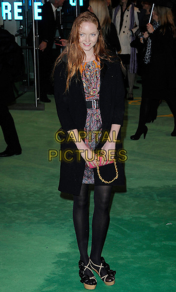 LILY COLE .Royal World Film Premiere of 'Alice in Wonderland' at the Odeon Cinema, Leicester Square, London, England..February 25th, 2010 .arrivals full length black coat waist belt pink red print pattern dress paisley tights.CAP/CAN.©Can Nguyen/Capital Pictures.