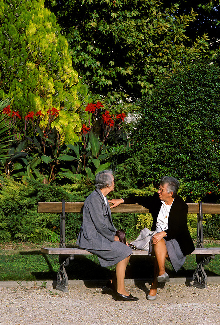 People, two women talking, sitting on park bench, city of Nimes, Languedoc Roussillon, France, Europe