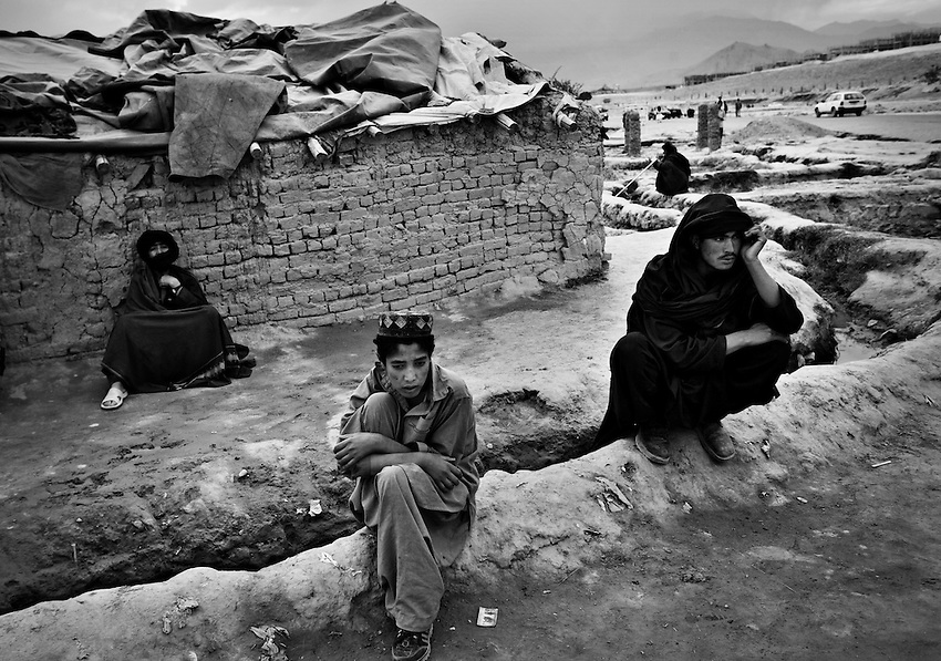 Displaced Pashtuns sit near an open sewer outside a meeting between displaced elders in the Chahari Qambar Camp, a tented slum community for displaced Afghans just west of Kabul, Afghanistan, Sunday, Oct 3, 2009.