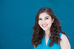 Portrait of a teenage girl with dark brown hair in a teal shirt against a teal wall