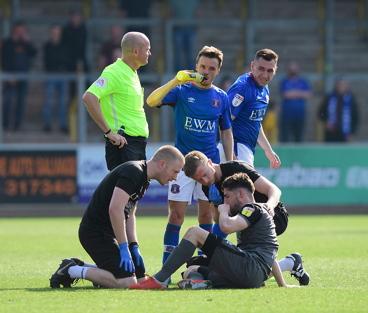 Lincoln City's Tom Pett receives treatment for an injury from Lincoln City assistant sports therapist Luke Treadwell, left, and Lincoln City's head of sports science and medicine Mike Hine<br /> <br /> Photographer Chris Vaughan/CameraSport<br /> <br /> The EFL Sky Bet League Two - Carlisle United v Lincoln City - Friday 19th April 2019 - Brunton Park - Carlisle<br /> <br /> World Copyright © 2019 CameraSport. All rights reserved. 43 Linden Ave. Countesthorpe. Leicester. England. LE8 5PG - Tel: +44 (0) 116 277 4147 - admin@camerasport.com - www.camerasport.com