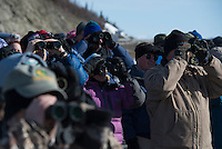 Birders gather at the Anchorage Audubon Society's annual Gunsight Mountain Hawkwatch on the Glenn Highway near Eureka, Alaska. On warm spring days hundreds of hawks may pass over the area, riding updrafts to higher altitude as they migrate through a bottleneck in the Talkeetna Mountains.