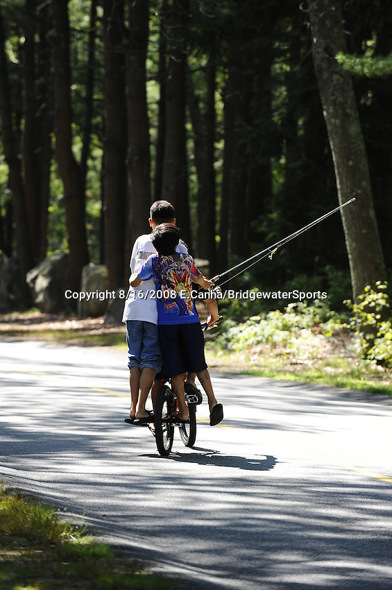 3 Asian children share a ride and a fishing pole on a summer afternoon